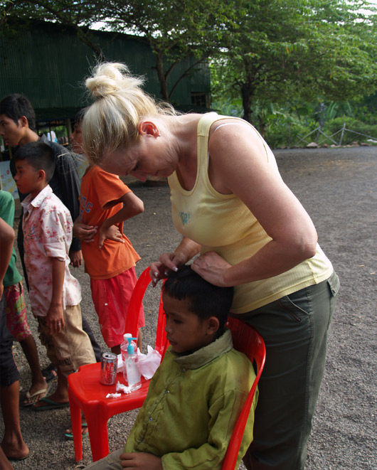 Katie checking for head  lice at Cambodia orphanage
